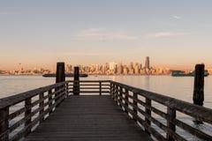 Pier in Seattle-Bucht mit Sonnenunterganglicht über im Stadtzentrum gelegenen Wolkenkratzern im Hintergrund, Washington, USA stockfoto