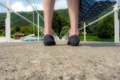 Pier seen between woman`s feet stock image