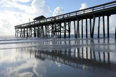 The pier sends a beautiful reflection to the beach floor royalty free stock photos