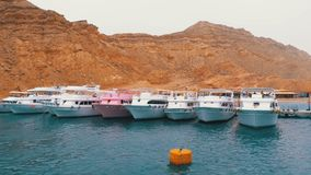 Pier with Ships and Yachts on the background of Mountains in the Desert of Egypt. View from the Boat at Sea to the Pier with Ships and Yachts on the background stock footage