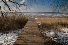 Pier on the shore of a frozen lake Stock Photo