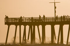 Pier Silhouette. Silhouette of Pismo Beach, California pier with waves splashing and people enjoying it Stock Image