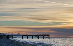 Pier silhouette in front of cloudy sunset sky. Pier silhouette in front of stripy blue cloudy sunset sky Stock Images