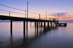 Pier silhouette over sunrise glow Stock Photo