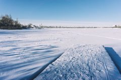 Pier in the snow and a frozen lake in the snow. Sunny winter day in the city Stock Image