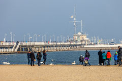 Pier in Sopot. Beach scene of many people walk on the shore in Valentines Day and wooden pier in the distance, on February 14, 2015 in Sopot, Poland Royalty Free Stock Photography