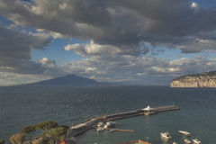 Pier in Sorrento. SORRENTO, ITALY - APRIL 16, 2014: Pier in Sorrento with stormy clouds over Vesuvius royalty free stock images