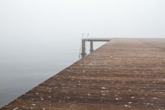 A pier and stairs under. A wooden pier and stairs to sea in a foggy day. Most of the photo is covered with the wooden pear royalty free stock image