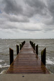 Pier on a Stormy Afternoon - Vertical. Vertical oriented image of a wooden pier on an stormy afternoon with looming dark clouds royalty free stock photography