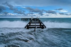 Pier in the stormy sea stock image
