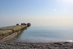 Pier stretching into the blue sea. In the haze Stock Photo