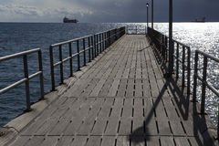 Pier stretching into the sea and the ships on the horizon. Stock Image
