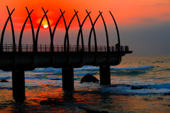 Pier and sunrise. Beautiful warm colorful sunrise over seaside pier, picture taken in Durban, south africa Royalty Free Stock Images