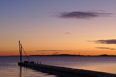 Pier before sunrise with birds sitting on a small crane silhouetted against the morning sky. Pier before sunrise with birds sitting on a small crane silhouetted Royalty Free Stock Photos
