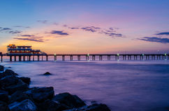 Pier at sunrise. A sunrise shot of the pier in Galveston, Texas. The lights are reflected on the sea below royalty free stock photos