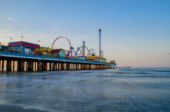 Pier at sunrise. A sunrise shot of the pier in Galveston, Texas. slow shutter speed makes the waves look soft royalty free stock photos
