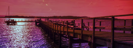 Pier at sunset. Bright coloured pink sky as the sunsets over the pier royalty free stock photo