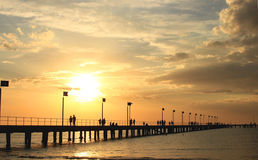 Pier, sunset, clouds and silhouettes Stock Photo