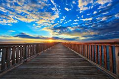 Pier into the sunset. Fishing pier on the Chesapeake bay in Maryland with the sun setting on the horizon stock photos