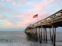 Pier at sunset. A flag waving on a pier at sunset Royalty Free Stock Photography