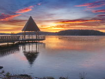 Pier at sunset. Pier at a frozen lake with a beautiful sunset Stock Photo
