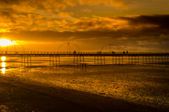 Pier at sunset. People in silhouette walking along victorian english pier at sunset royalty free stock photos