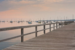 Pier at sunset with sailboats on the background. Stock Images