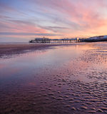 Pier at Sunset. Victorian Pleasure Pier at sunset reflected in a wet beach stock photography