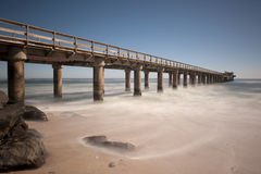 Pier at Swakopmund. Mist between the rocks with pier in the background Stock Image