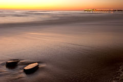 Pier at Swakopmund 2. Reflection of sunset with rocks in foregroundand pier in the background Royalty Free Stock Images