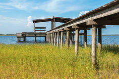 Pier to boathouse on water. Wooden pier or dock above grass leading to empty boathouse shelter structure on water river lake intracoastal waterway ocean Royalty Free Stock Photo