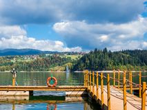 Pier to the lake with lifebuoy, mountains and cloudy sky, view of the sailboat and the village stock photos