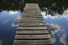 Pier to Nowhere. Fishing Pier seemingly expanding out into the reflection of the sky and clouds Royalty Free Stock Images