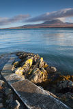 Pier to water's edge, overlooking the mountains of Jura Royalty Free Stock Photo