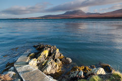 Pier to water's edge, overlooking the mountains of Jura. Scotland UK. Taken from Islay on a still clear day in November. The mountains opposite are known as Stock Image
