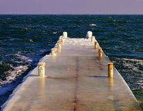 Pier in the translucent ice. In sunny day on the northern coast of the Black Sea. Odessa, Ukraine Stock Photos