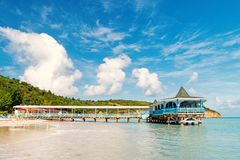 Pier in turquoise water on blue sky background. Sea beach with wooden shelter on sunny day in antigua. Summer vacation. On caribbean. Wanderlust, travel, trip royalty free stock images
