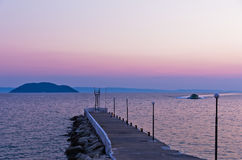 Pier at twilight with turtle island in a background, near the city of Neos Marmaros in Sithonia Stock Photography