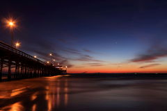 Pier Twilight. A view of pier after the sunset with street lights and reflection on the oceann Stock Photo