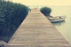 Pier und Boot am Seeufer Stockbilder