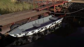 Pier und hölzernes Boot am See stock footage