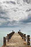 Pier under Dark Clouds Stock Photo