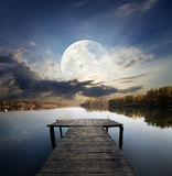Pier under moon. Fishing pier on a river under fool moon. Elements of this image furnished by NASA Stock Images