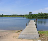 Pier Walk. Long wooden pier on a lake with boat in background Stock Photo