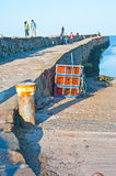 Pier walk on harbor wall at St Andrews. Fife also showing lobster pots stock images