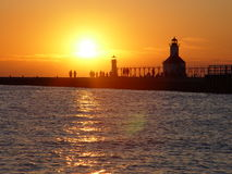 Pier Walking Sunset. The Saint Joseph, Michigan sunsets beyond the two piers are fascinating.  This shot brought together the silhouettes of people walking Royalty Free Stock Photography