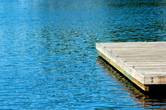 Pier and water. Wooden pier with metal eye hooks surrounded by deep blue water with ripples Royalty Free Stock Photos