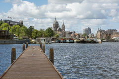 Pier on the water in Amsterdam with boats and building as background in the day Stock Images