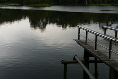 Pier at the waterside of the pond in the evening Royalty Free Stock Photos