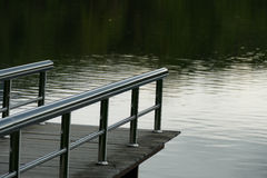 Pier at the waterside of the pond in the evening Stock Image